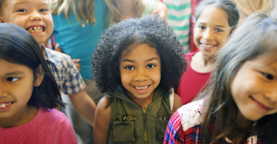 Diverse children gather ready to learn at school