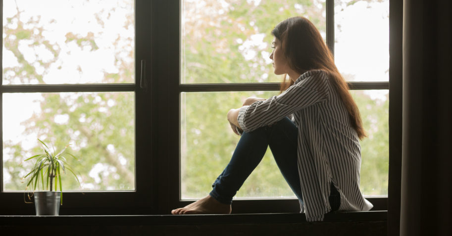 Woman struggling with depression watches out window
