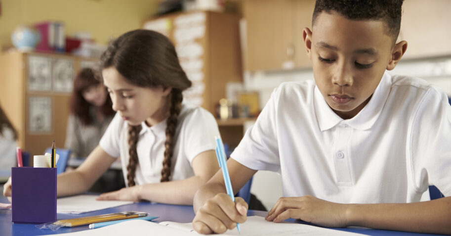 Diverse students take a test in a Christian school classroom